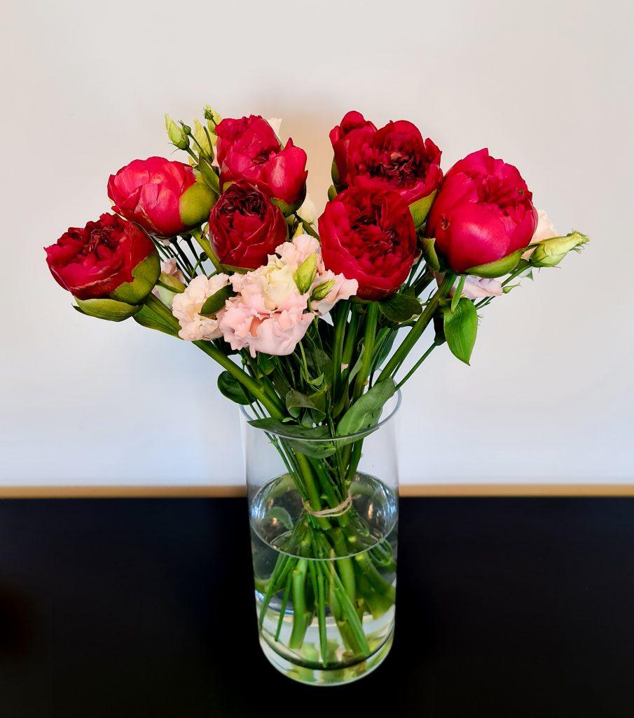 rote Pfingstrosen mit rosa Lisianthus