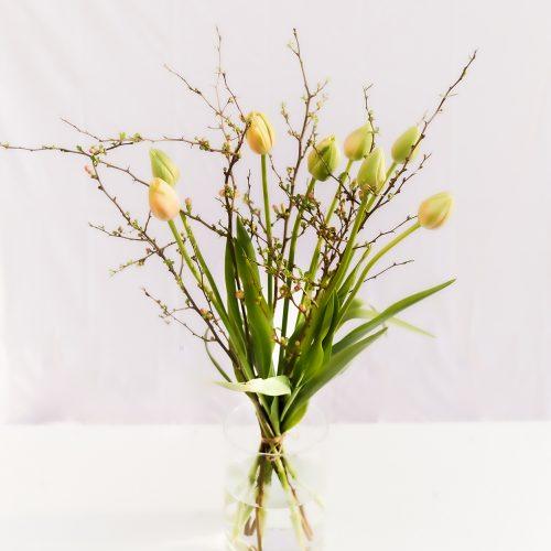 Tulpenstrauß mit orangen langen Tulpen und Quittenzweigen